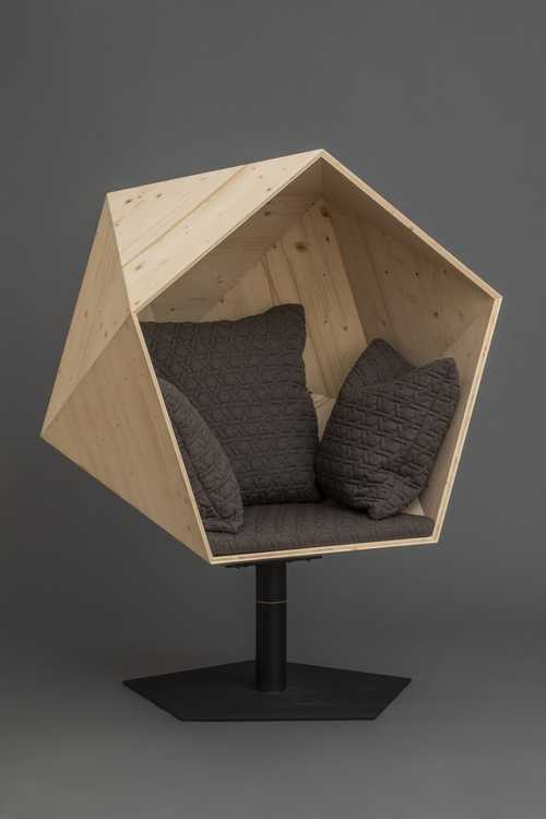 Soft chair enclosed in a geometric shell on pedestal