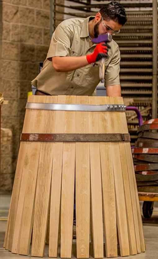 Cooper making a wood wine barrel